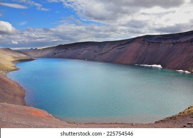 Oval blue lake in the crater of the volcano cooled down. Steep banks of the lake of red rhyolite. Iceland in July