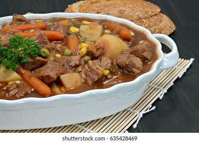 An oval casserole of homemade beef stew with vegetables and garnished with parsley.
