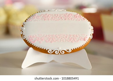 An oval cookie,covered with white glaze, decorated pink pattern stands on the restaurant plate in front of festive candybar with differnt desserts, yellow cupcakes and berry jellies.