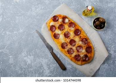 Oval Italian pizza with tomato and salami Pepperoni on gray concrete background. Selective focus. Top view. Copy space.