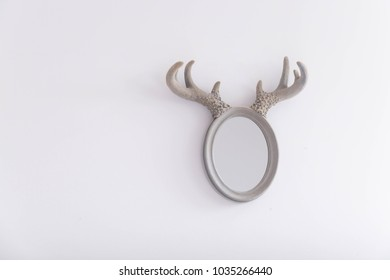 Oval mirror with horns on the white painted wall