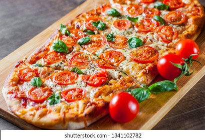oval Pizza with Mozzarella cheese, Tomatoes, pepper, Spices and Fresh Basil. Italian pizza. Pizza Margherita or Margarita on wooden table background
