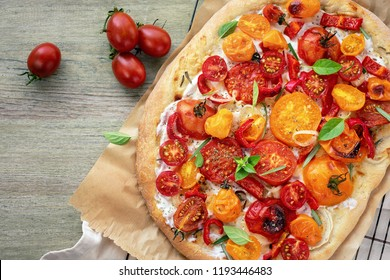 Oval pizza with yellow and red cherry tomatoes, ricotta cheese and basil on a wooden table.