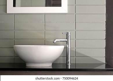 Oval shape ceramic sink with modern stainless faucet in the bathroom.