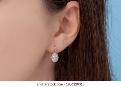 Oval silver earrings attached to a well-groomed lady's ear on a blue background
