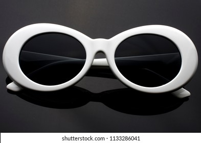 oval sunglasses in white plastic frame isolated on black