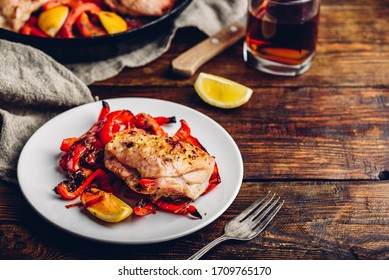 Oven baked chicken thighs with red bell peppers and lemon on white plate.