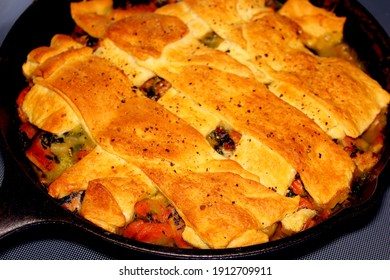 Oven baked dinner in a skillet, strips of crispy biscuit crescent roll lattice across the top.