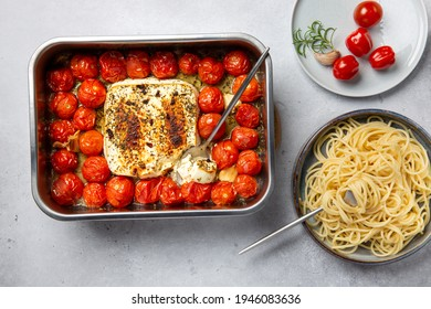 Oven baked feta pasta made of cherry tomatoes, feta cheese, garlic and herbs. Fetapasta on gray background. Trending viral recipe. Top view.