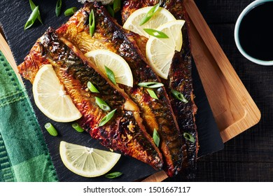 Oven baked grilled mackerel or saba shioyaki fish filled with omega 3 fatty acids served with rice, soya sauce, lemon, chive on a black cutting board on a dark wooden background, overhead