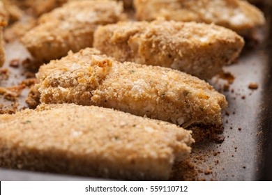 Oven Baked Parmesan Crusted Chicken Tenders on a seasoned baking stone