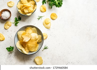 Oven baked  potato chips in bowls. Homemade crispy potato chips on white background, top view, copy space.