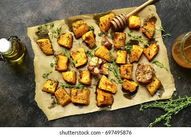 Oven baked pumpkin slices with garlic and thyme served with honey.Top view.