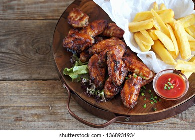 Oven baked spicy barbecue chicken wings with potato fries.