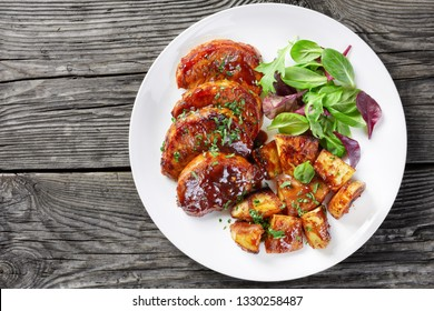 Oven Baked sticky glazed Pork Chops with baked Potatoes served with fresh green salad on a white plate on a rustic table, view from above, close-up, flatlay