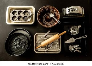 Backwaren - Backwaren, Backwaren und Küchenutensilien. Sammlung von oben (oberste Ansicht, flache Lage). Hintergrund mit schwarzer Tafel.