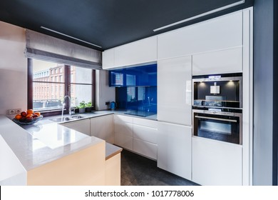 Oven built in white cabinets and blue glaze in modern kitchen interior with window