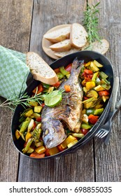 Oven fresh gilthead baked with rosemary on mixed summer vegetables, served with Italian ciabatta bread