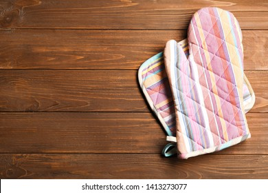 Oven glove and potholder on wooden background, flat lay. Space for text