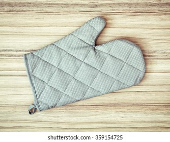 Oven mitt (glove) or potholder on the wooden background.