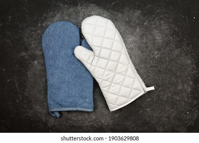 Oven Mitts On Black Grunge Background. Pair Of Protective Grill Gloves On Black Rough Table. BBQ Mitts Or Gloves On Rough Black Surface.