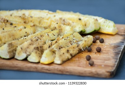 Oven roasted parmesan garlic zucchini spears.  Zucchini season. Zucchini dish. Close-up. Zucchini on a wooden desk.