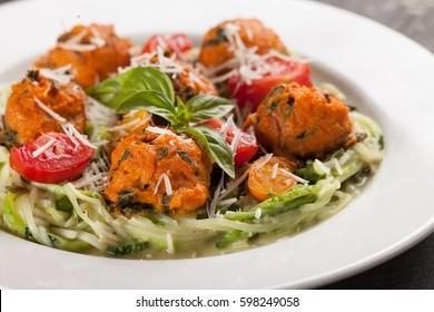 Oven roasted sweet potato balls on sautéed zucchini on dark wooden background macro shot