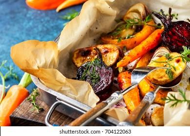 Des légumes grillés au four avec de l'ail et des herbes sur le plateau de cuisson. Les racines de légumes d'automne à hiver.