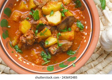 Oven stewed potatoes with chicken liver and tomatoes sauce in a traditional Moldovan clay plate. Served with fresh parsley. Wooden spoon, fresh garlic,and parsley leaves on a table.