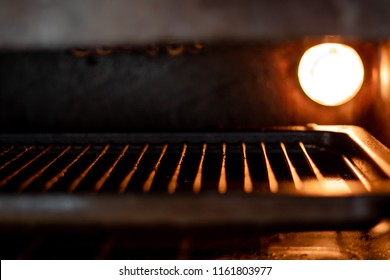 Oven Tray in Oven with Bright Orange Light on Illuminating metal and tray. Grill/Oven Appliance, Cooker