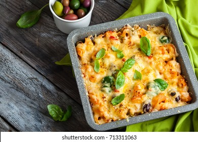 Oven-baked pasta with colourful olive, peppers and tomatoes. Pasta and vegetables gratin in baking dish