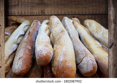 Oven-fresh baguette in a wooden box