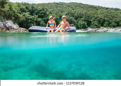 Over the deep blue sea: two childs float on inflatable mattress in the sea lagoon