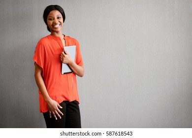 Over eager businesswoman smiling at camera while holding a digital tablet in on hand.