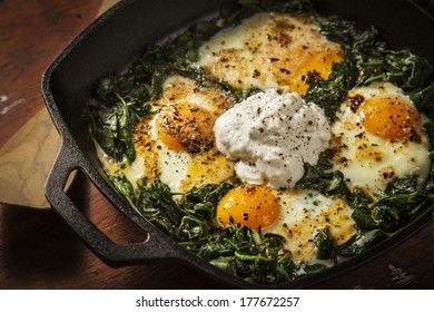 Over easy eggs with Spinach and Garlic in a Cast Iron Skillet on a Wooden Table With a Spatula