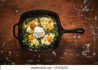 Over easy eggs with Spinach and Garlic in a Cast Iron Skillet on a Wooden Table