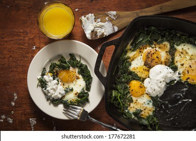 Over easy eggs with Spinach and Garlic in a Cast Iron Skillet on a Wooden Table With a Spatula Served with Orange Juice