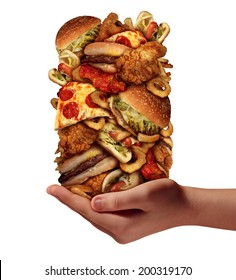 Over eating and compulsive indulgence of fast food concept as a hand holding up a huge stack of junk food as hamburgers hotdogs and french fries as an unhealthy diet and bad nutrition symbol.