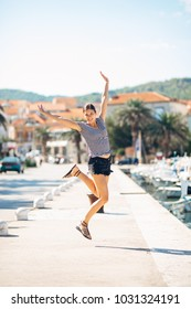 Over exited happy woman jumping in the air out of happiness.Vacation time concept.Seaside coastal vacation excitement.Woman in joy got good news.Rejoicing,full of life.Summer female active,energetic