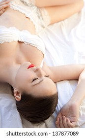 Over head beauty portrait of a young woman peacefully laying down in bed wearing white lingerie and red lips.