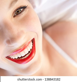 Over head beauty portrait of a young woman's half face laying down in bed wearing white lingerie and red lips, smiling at the camera.