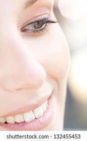Over head close up beauty portrait of a young caucasian healthy woman face and eye looking down with long eyelashes and sparkling lights in the background.