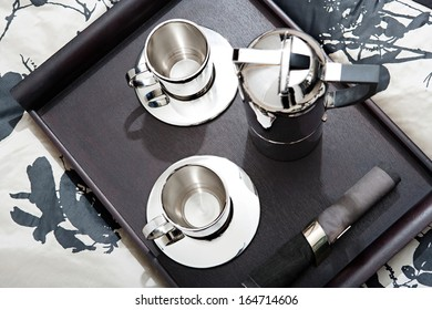 Over head close up view of an elegant wooden tray on a hotel soft bed cover with a shining exclusive silver set of coffee for two, with coffee maker and two cups. Home interior with no people.