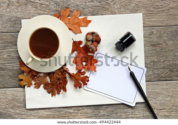 Over head flat lay desk top with fall leaves, coffee cup  and saucer, pen and ink, white blank stationary.