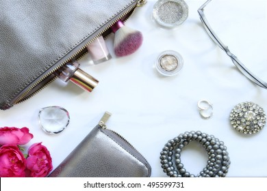 Over head flat lay marble make up table with silver metallic accents, make up, pink flowers, silver sparkly jewlery, eyeglasses and a cup of glitter.