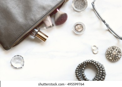 Over head flat lay marble make up table with silver metallic accents, make up, silver sparkly jewlery, eyeglasses and a cup of glitter.