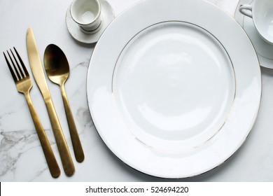 Over head flat lay view of white and gold fine china place setting. Gold silverware and elegant china.
