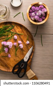 Over head photo of chives blossoms being cut with sissors from stems and placed in a wooden bowl.