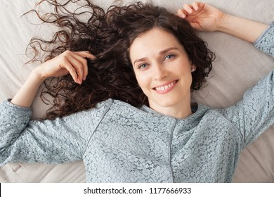 Over head portrait of beautiful middle age woman laying on bed smiling looking at camera with blue eyes and curly hair, home interior. Healthy female fresh skin care, leisure lifestyle indoors.
