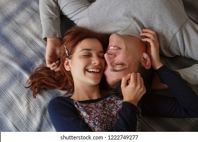 Over head portrait of a beautiful young couple laying on bed with heads togheter laughing joyfully, sharing fun romantic moments, home interior. Lovers lifestyle of love and affection indoors.
